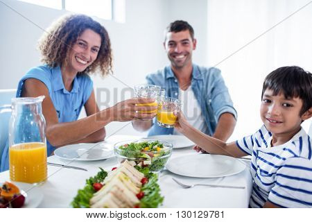 Portrait of family toasting glasses of orange juice while having breakfast at home