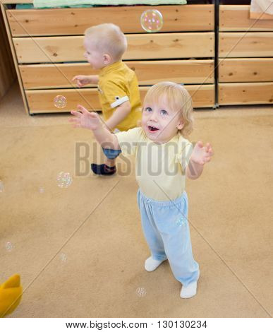 Children playing with soap bubbles in day care centre