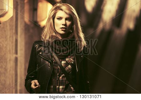 Young fashion blond woman in leather jacket walking in a subway