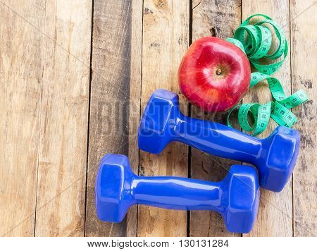 Blue dumbbell measuring tape and red apple on wooden table. Fitness concept