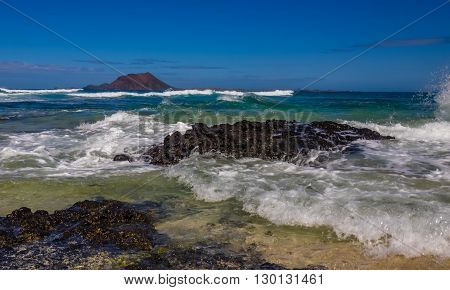 Waves hitting the shore  in Corralejo Dunes National Park in Fuerteventura, Canary Island, Spain with Los Lobos Island in the background