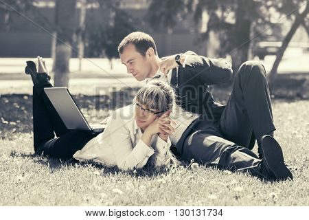 Young business people using laptop in a city park