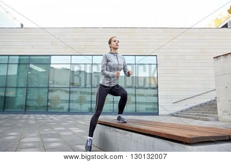 fitness, sport, training, people and lifestyle concept - young woman making step exercise on city street bench