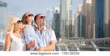 summer holidays, travel, tourism, vacation and people concept - happy family over dubai city street background