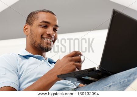 Young black man using laptop computer, smiling happy. High angle view.