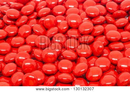 red sugar coated pills tablets vitamin on white background