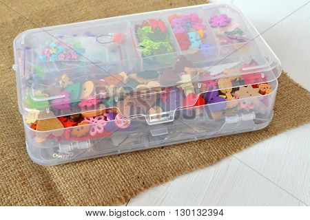 A set of different buttons in a organizer on a burlap