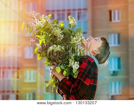 Happy girl with big bouquet of flowers laughing happily in the sun on a background of a new, multi-storey building - new building. Concept - happiness, joy, buying apartments, new housing, mortgage, real estate, sales,
