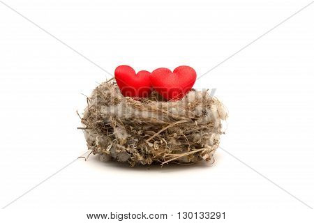 Souvenir red hearts in natural bird's nest made from grass and fluff