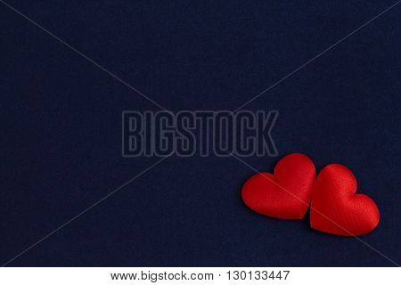 Dark background from a violet velvet and two red hearts on the right below