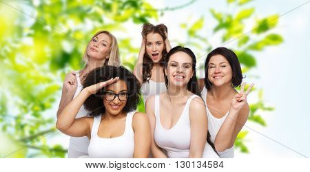 friendship, beauty, body positive and people concept - group of happy plus size women in white underwear having fun and making faces over green natural background