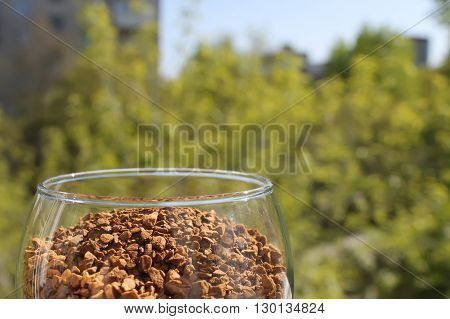 wine glass with granulated coffee left on the background of the city