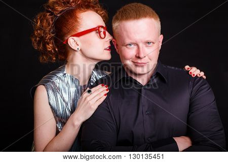 redhead couple. red-haired girl something seductively whispering in the ear of the red-haired man. Black background
