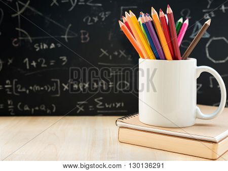 Crayon and book on school table with blackboard background.