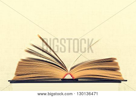 The opened book with the turned yellow pages on a light background from weaving