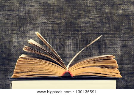 The opened book with the turned yellow pages against a dark background from weaving