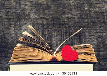 The opened book with the turned yellow pages and heart against a dark background from weaving