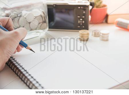 hand writing on the paper with financial planning concept.