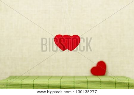 Two red hearts hang on threads on a light background and the third in the distance
