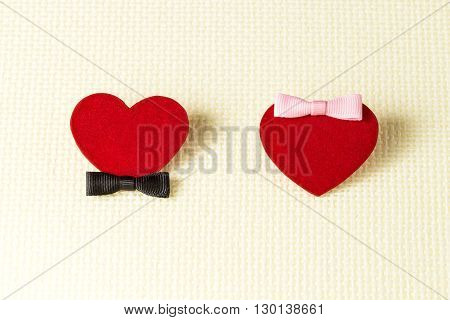 Red man's and female hearts with black and pink bows on a light checkered background