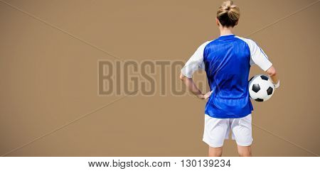 Rear view of woman football player posing against maroon background