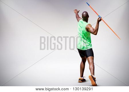 Rear view of man throwing javeline against white background against grey background