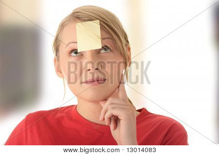 Young woman in red tshirt with yellow sticky note on forehead.