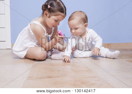 Baby brother and toddler sister playing doctor with syringe