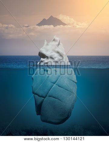 Big rock like iceberg floating in blue ocean with mountain peak in background at warm day. Global warming concept.