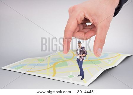 Portrait of happy man holding camera against city map