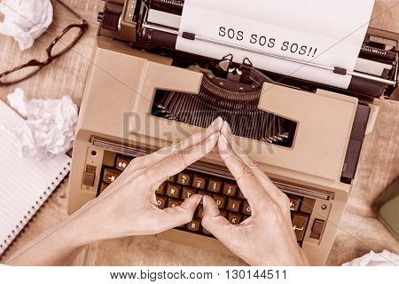 SOS message on a white background against above view of typewriter and old phone