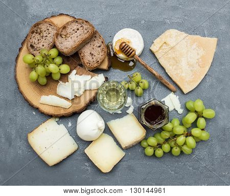 Cheese appetizer selection or wine snack set. Variety of italian cheese, green grapes, bread slices and honey on round wooden board over grey concrete textured backdrop, top view, horizontal