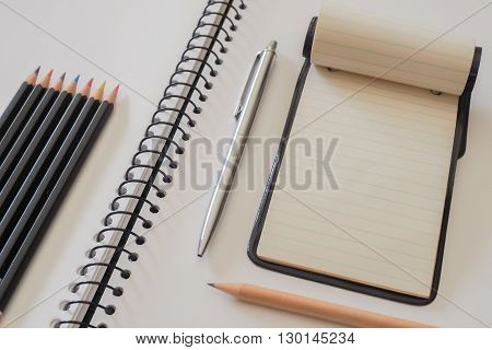 A small note pad on a larger spiral bound sketch pad with a silver cased pen a plain lead pencil and a group of colored pencils.