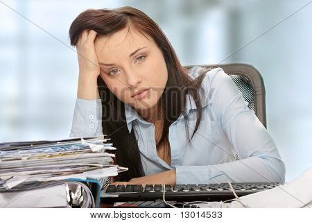 Exhausted female filling out tax forms while sitting at her desk.