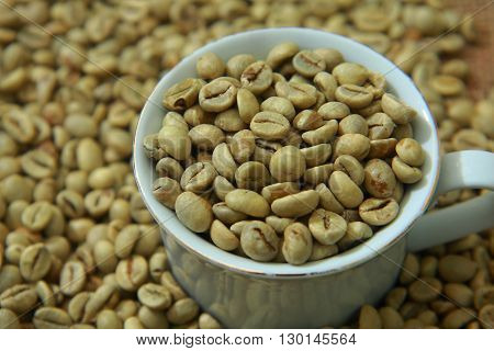Raw coffee beans in white cup with blurred coffee beans on background