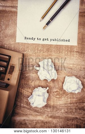 Ready to get published message on a white background against view of an old typewriter and paper