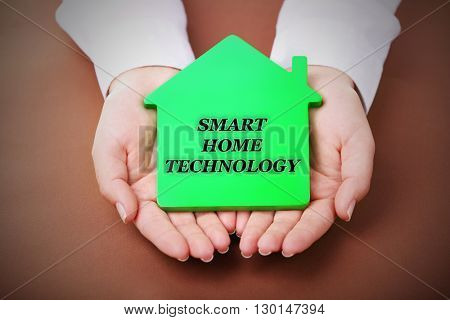 Smart home technology concept. Female hands holding house on brown background