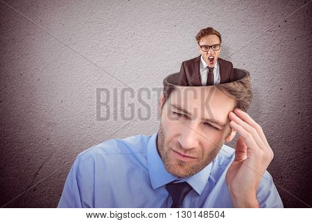 Young angry businessman shouting at camera against grey wall