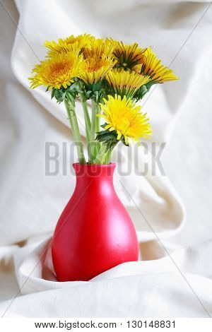 Bunch of yellow dandelions in nice red vase on white cloth