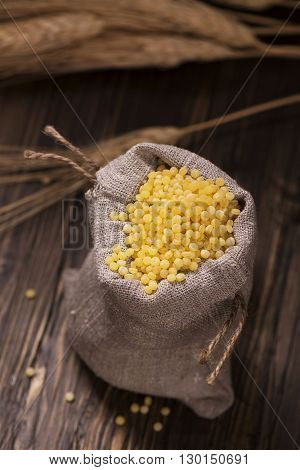 Golden pearl couscous in a burlap bag and spikelets over grunge wooden table. Vintage style