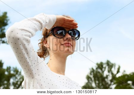 Young white-skinned girl with sunglasses is covering by hand her eyes from the sun and looking into the distance