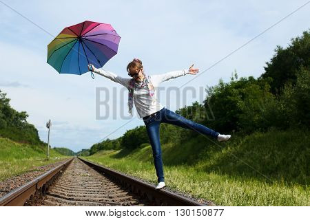 Young white-skinned girl is walking on the rails with colorful umbrella in her hand in sunny summer day