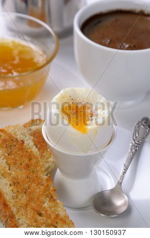 Soft-boiled egg with cup of coffee toast and jam for breakfast