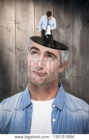 Businessman shouting through megaphone against bleached wooden planks background