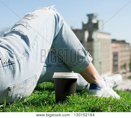 Woman Resting On The Grass With Cup Of Coffee.