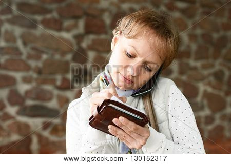 Young girl is smiling talking by phone and writing down some information in pencil on paper at stone wall background