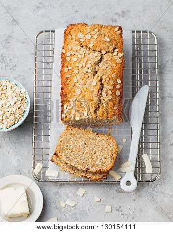 Healthy vegan oat and coconut loaf bread, cake on a cooling rack Grey stone background Top view
