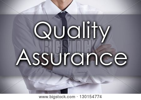 Quality Assurance - Young Businessman With Text - Business Concept