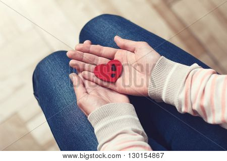 Girl is keeping at her palms red heart with black footprint of man's shoe. Past relationships concept