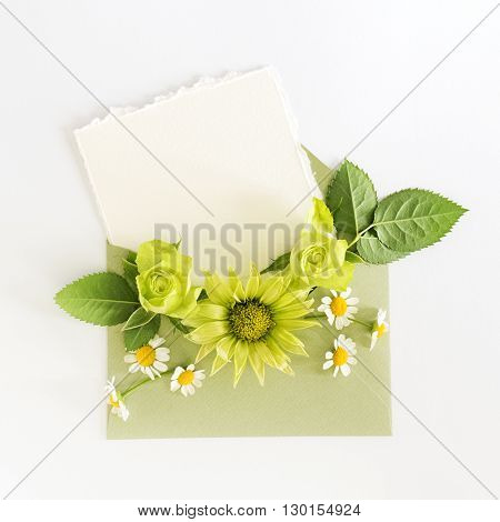 Empty cardboard card with flowers and an envelope on white background. Flat lay. Top view.
